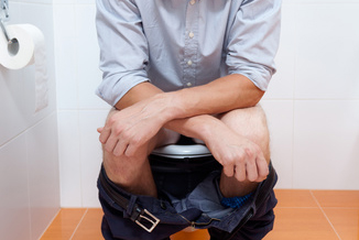 Vertical view of a businessman in toilet