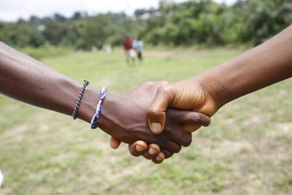 epa04901092 Liberians shake hands in Nyehn Town, Todee District in a suburb outside Monrovia, Liberia, 27 August 2015. Reports state that complacency has overwhelmed Liberians, as people returns to normal handshake, which is forbiden, as a measure to combat the spread of the deadly ebola disease. Liberia has made a significant number of days in its 42 days countdown to regain its Ebola-free status for the second time within in a year. Liberia was declared Ebola-free by WHO on 09 May 2015, but, on 29 June 2015, the emergence of a new case involving a 17 year-old boy whose corpse tested positive of the virus 48 days after the nation was declared free of ebola. EPA/AHMED JALLANZO